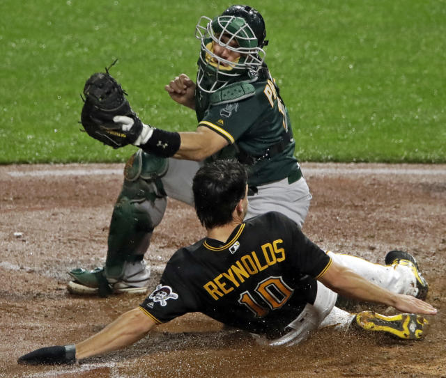 Pittsburgh Pirates' Bryan Reynolds (10) scores ahead of the tag by Oakland Athletics catcher Josh Phegley during the seventh inning of a baseball game in Pittsburgh, Saturday, May 4, 2019. (AP Photo/Gene J. Puskar)