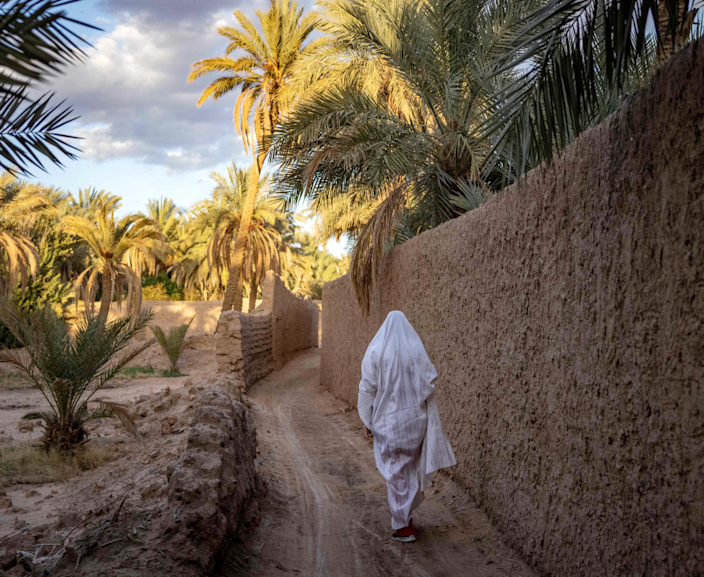 A woman walks past a mud wall in Figuig surrounded by palm trees on Morocco's border with Algeria - Saturday 20 March 2021