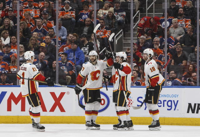 Calgary Flames' Mikael Backlund (11), Michael Frolik (67), Rasmus Andersson (4) and James Neal (18) celebrate a goal against the Edmonton Oilers during the second period of an NHL hockey game in Edmonton, Alberta, Saturday, Jan. 19, 2019. (Jason Franson/The Canadian Press via AP)