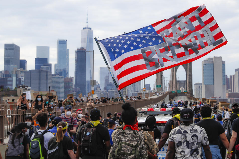 """FILE - Protesters march on the Brooklyn Bridge, Thursday, June 4, 2020, in New York under a U.S. flag with the slogan """"I can't breathe."""" Protests continued following the death of George Floyd, who died after being suffocated by Minneapolis police officers on May 25. (AP Photo/John Minchillo, File)"""