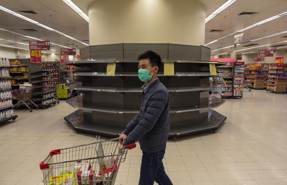 A man shopper wearing a face mask walks past empty supermarket shelves, usually stocked with toilet paper and kitchen rolls. The death toll from the covid-19 coronavirus epidemic past 1, 100 and infected over 45, 000 people worldwide on february 12. A shopper wearing a face mask walks past empty supermarket shelves, usually stocked with toilet paper and kitchen rolls. The death toll from the covid-19 coronavirus epidemic past 1, 100 and infected over 45, 000 people worldwide on february 12. (Photo by Miguel Candela / SOPA Images/Sipa USA)