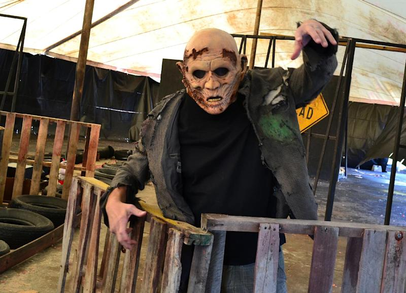 This undated image provided by Saint Lucifer's Haunted Asylum in Flint, Mich., shows a zombie awaiting his fate from paintball-shooting visitors. Saint Lucifer's is offering a shoot-the-zombie game, part of a trend in which Halloween attractions are becoming more interactive. Instead of walking through a haunted house as a passive observer, guests are now being invited to partake in challenges and games of various sorts. (AP Photo/ Saint Lucifer's Haunted Asylum)