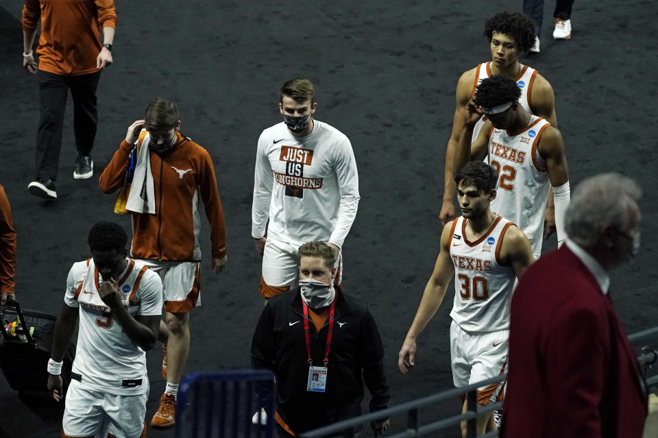 Texas players leave the court after losing to Abilene Christian in a college basketball game in the first round of the NCAA tournament at Lucas Oil Stadium in Indianapolis Sunday, March 21, 2021. (AP Photo/Mark Humphrey)