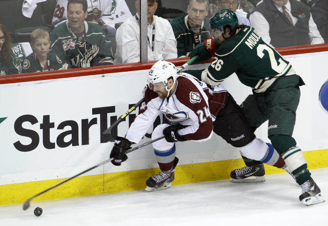 2Colorado Avalanche right wing Marc-Andre Cliche (24) and Minnesota Wild left wing Matt Moulson (26) chase the puck during the first period of Game 3 of an NHL hockey first-round playoff series in St. Paul, Minn., Monday, April 21, 2014. (AP Photo/Ann Heisenfelt)