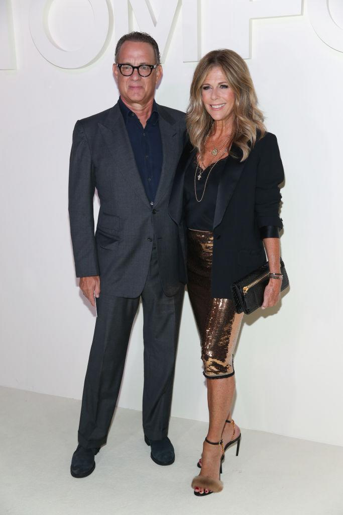 <p>Tom Hanks and Rita Wilson attend Tom Ford's spring/summer 2019 fashion show at the Park Avenue Armory on Sept. 5, 2018, in New York City. Hanks wore a grey Windsor peak-lapel suit with a classic day shirt by Ford. His wife, Rita, wore a gold liquid-sequin pencil skirt, heels, and clutch by the designer and paired the look with a black blouse and blazer. (Photo: Rob Kim/WireImage) </p>