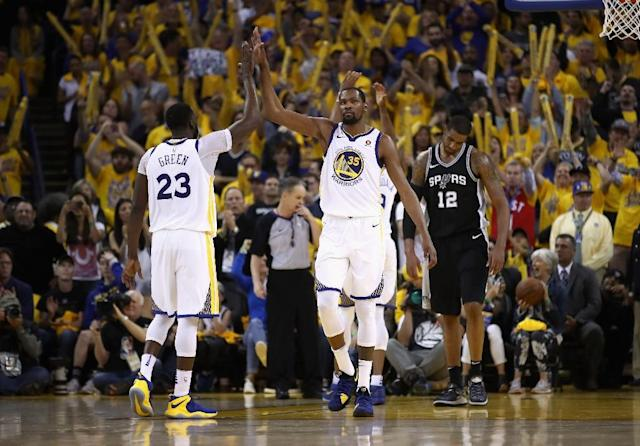 Kevin Durant (R) high fives Draymond Green as the Golden State Warriors power into the Western Conference playoff semi-finals with a 4-1 series victory over the San Antonio Spurs (AFP Photo/EZRA SHAW)