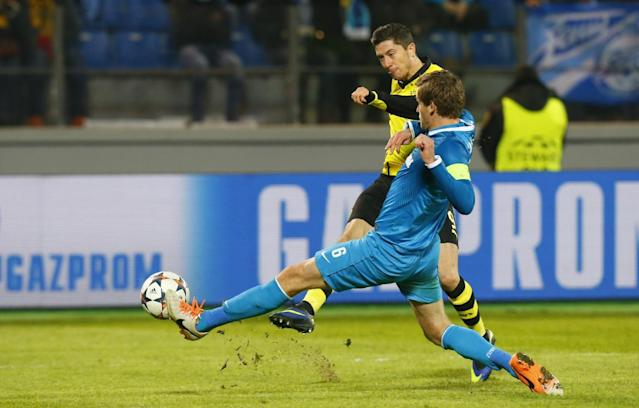 Borussia's Robert Lewandowski tries to score against Zenit's Nicolas Lombaerts during the Champions League soccer match between Zenit St.Petersburg and Borussia Dortmund at Petrovsky stadium in St.Petersburg, Russia, on Tuesday, Feb. 25, 2014. (AP Photo/Dmitry Lovetsky)
