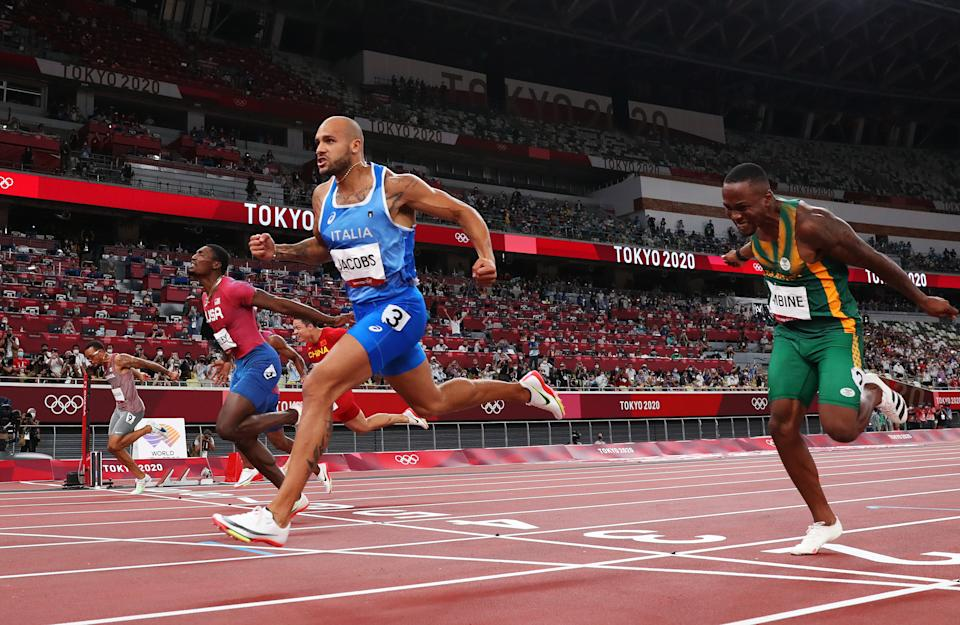 Italy's Marcell Jacobs (in blue) wins the men's 100m final at the Tokyo Olympic Stadium at the 2020 Tokyo Olympics.