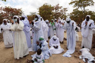 Members of an Apostolic Christian Church group gather for a prayer meeting on the outskirts of the capital Harare, Friday, Sept. 10, 2021. The Apostolic church is one of Zimbabwe's most skeptical groups when it comes to COVID-19 vaccines. Many of these Christian churches, which combine traditional beliefs with a Pentecostal doctrine, preach against modern medicine and demand followers seek healing or protection against disease through spiritual means like prayer and the use of holy water. To combat that, authorities have formed teams of campaigners who are also churchgoers to dispel misconceptions about the vaccines in their own churches. (AP Photo/Tsvangirayi Mukwazhi)