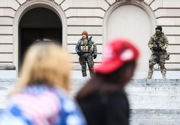 Two militia members keep watch at the front of Kentucky's state Capitol as about 40 people marched in honor of Ashli Babbitt, the Air Force veteran who was shot and killed by a U.S. Capitol Police officer on Jan. 6.