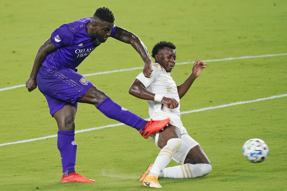 Orlando City forward Daryl Dike, left, takes a shot on goal past Atlanta United defender George Bello during the first half of an MLS soccer match Wednesday, Oct. 28, 2020, in Orlando, Fla. (AP Photo/John Raoux)