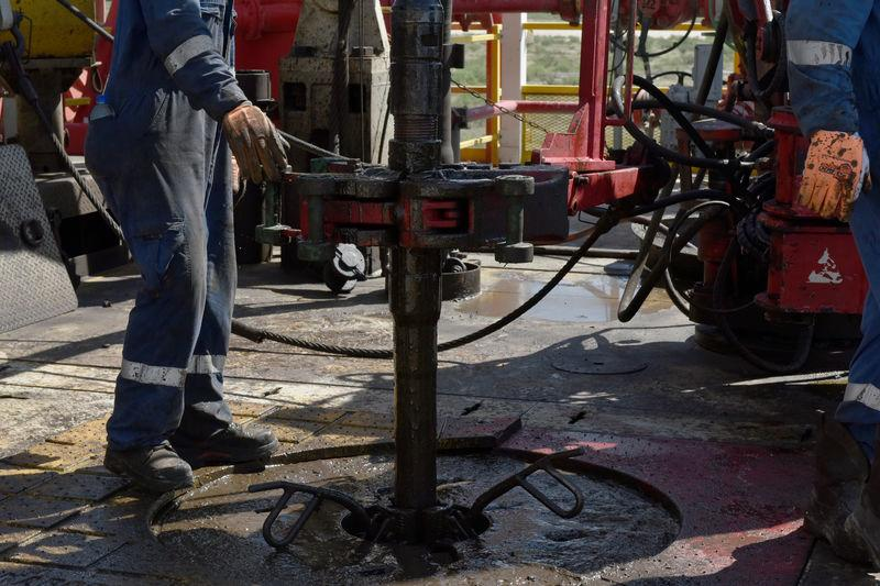 A drilling crew uses a mechanical roughneck machine to thread drill pipe together on an oil rig in the Permian Basin near Wink