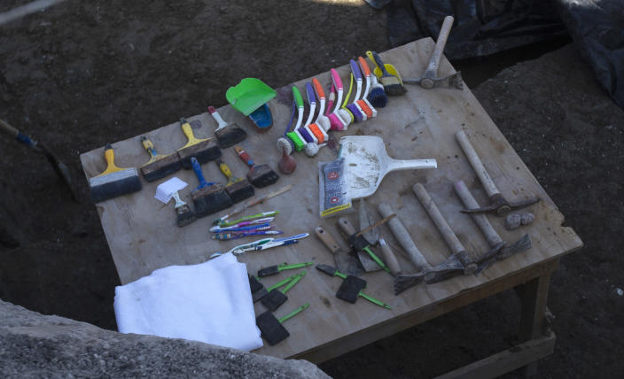 Paleontologists' tools sit on a table as they work to preserve the skeleton of a mammoth that was discovered at the construction site of Mexico City's new airport in the Santa Lucia military base, Mexico, Thursday, Sept. 3, 2020. The paleontologists are busy digging up and preserving the skeletons of mammoths, camels, horses, and bison as machinery and workers are busy with the construction of the Felipe Angeles International Airport by order of President Andres Manuel Lopez Obrador. (AP Photo/Marco Ugarte)