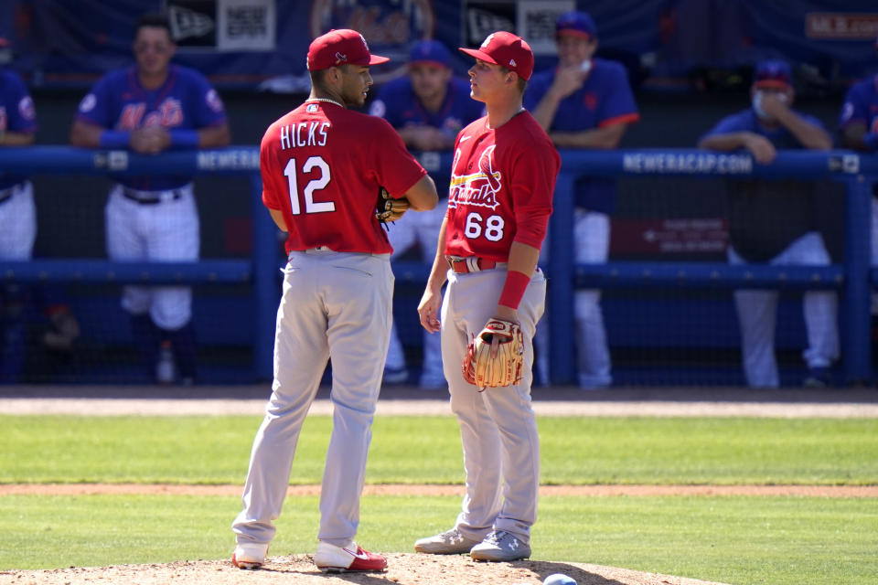 St. Louis Cardinals relief pitcher Jordan Hicks (12) talks with third baseman Nolan Gorman (68) after walking New York Mets' Luis Guillorme during the fifth inning of a spring training baseball game, Sunday, March 14, 2021, in Port St. Lucie, Fla. (AP Photo/Lynne Sladky)