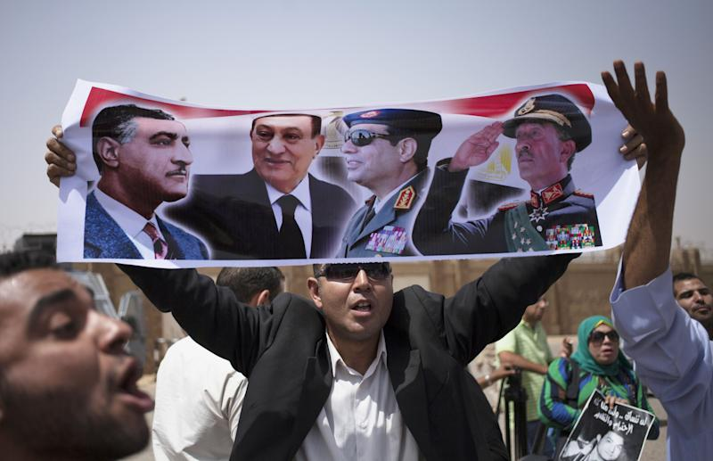 Supporters holding pictures of Egypt's ousted President Hosni Mubarak rally outside a courtroom in Cairo Saturday, June 8, 2013. (AP Photo/Khalil Hamra)