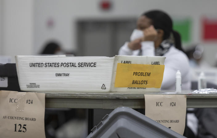 A box labeled for problem ballots sits on a table while election workers sort through absentee ballots in Detroit.