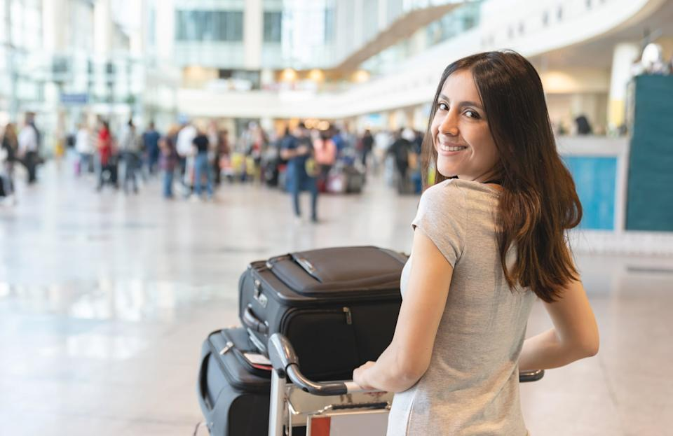 Female traveler at the airport carrying her luggage on a cart and looking at the camera smiling - travel concepts