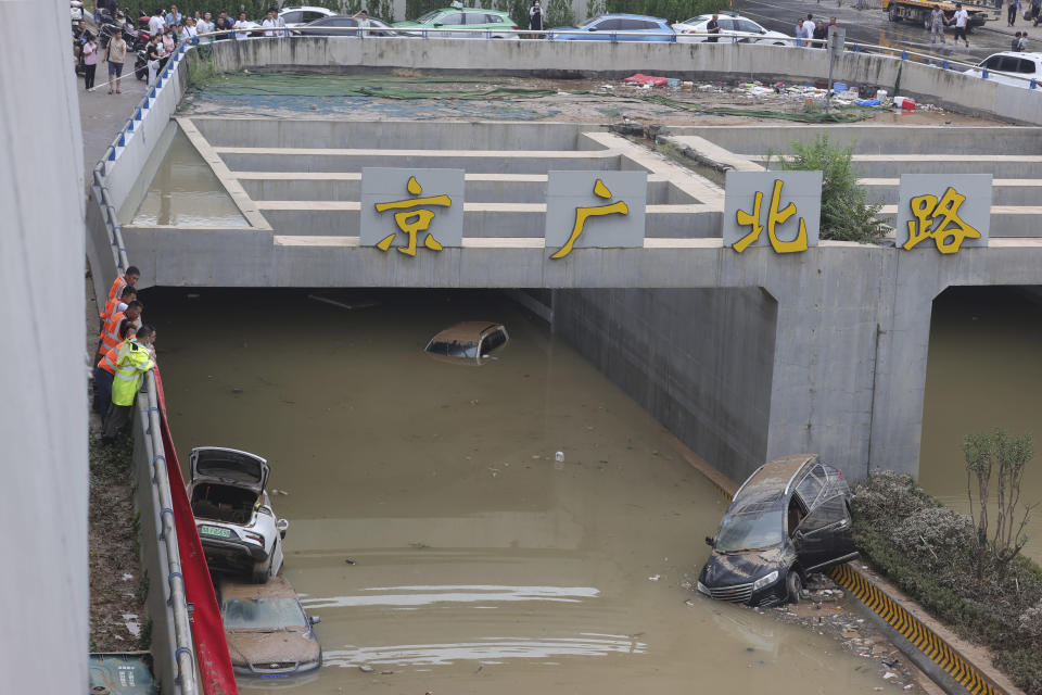 Rescuers watch as water is pumped from a road tunnel feared to be filled with vehicles caught in floodwaters in Zhengzhou in central China's Henan Province, Friday, July 23, 2021. The death toll from catastrophic flooding in the central Chinese city of Zhengzhou has continued to rise, state media reported Friday. The official China Daily newspaper and other media said the number included just Zhengzhou, the capital of Henan province. Other areas of the province have also faced heavy downpours, and rivers and reservoirs burst their banks. (Chinatopix via AP)