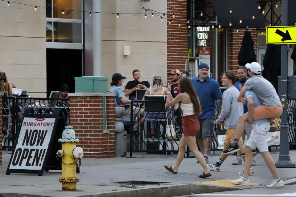 FILE - In this June 28, 2020, file photo, people gather at tables outside Bar Louie on the Northside of Pittsburgh. Authorities are closing honky tonks, bars and other drinking establishments in some parts of the U.S. to stem the surge of COVID-19 infections — a move backed by sound science about risk factors that go beyond wearing or not wearing masks. (AP Photo/Gene J. Puskar, File)