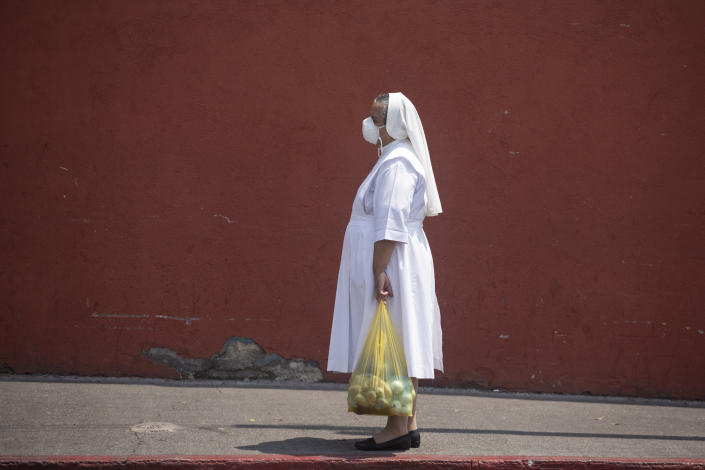 A nun, waring a mask to protect herself from the spread of the new coronavirus, stands near the closed Candelaria church in Guatemala City, Wednesday, April 8, 2020. Catholics prepare to celebrate Holy Week amid measures to prevent the spread of the coronavirus, including stopping all religious activities across the country. (AP Photo/Moises Castillo)