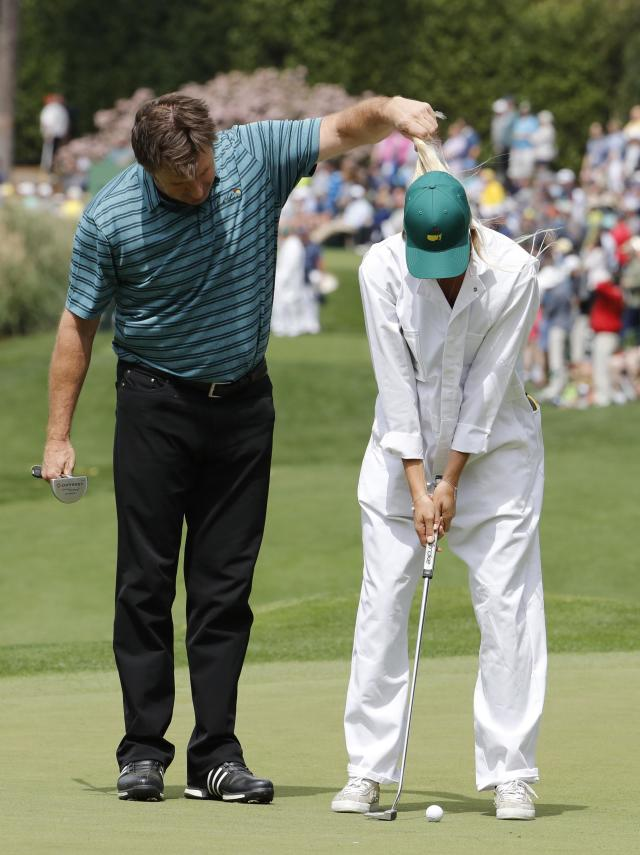 Nick Faldo of England holds the hair of Sofia, wife of Spanish golfer Rafael Cabrera-Bello, during the par 3 contest held on the final day of practice for the 2018 Masters golf tournament at Augusta National Golf Club in Augusta, Georgia, U.S. April 4, 2018. REUTERS/Jonathan Ernst