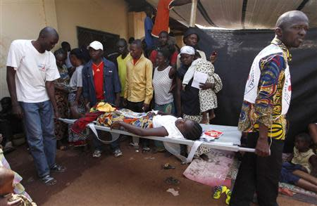 Men carry a pregnant woman on a stretcher from the Medecins Sans Frontieres clinic to a hospital in Bangui December 12, 2013. REUTERS/Emmanuel Braun