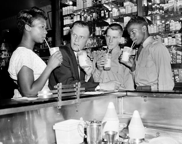 "<p>Evangelist Billy Graham enjoys an ice cream soda with a group of teenagers after discussing the problem of juvenile crime with a group of youngsters at a New York City news conference on Aug. 8, 1957. At the Hotel New Yorker, Graham proposed that passages from the Bible be read ""in every classroom in New York City"" as a way of combating teenage crime. (Photo: AP) </p>"