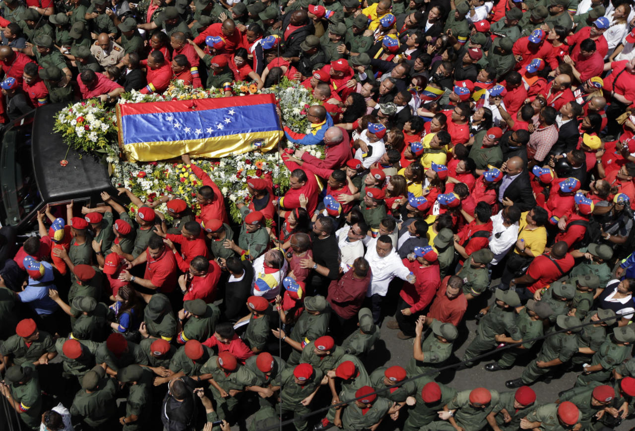 People walk alongside the flag-draped coffin containing the body of Venezuela's late President Hugo Chavez from the hospital where he died, to a military academy where it will remain until his funeral in Caracas, Venezuela, Wednesday, March 6, 2013. Seven days of mourning were declared, all schools were suspended for the week and friendly heads of state were expected for an elaborate funeral Friday. (AP Photo/Ariana Cubillos)
