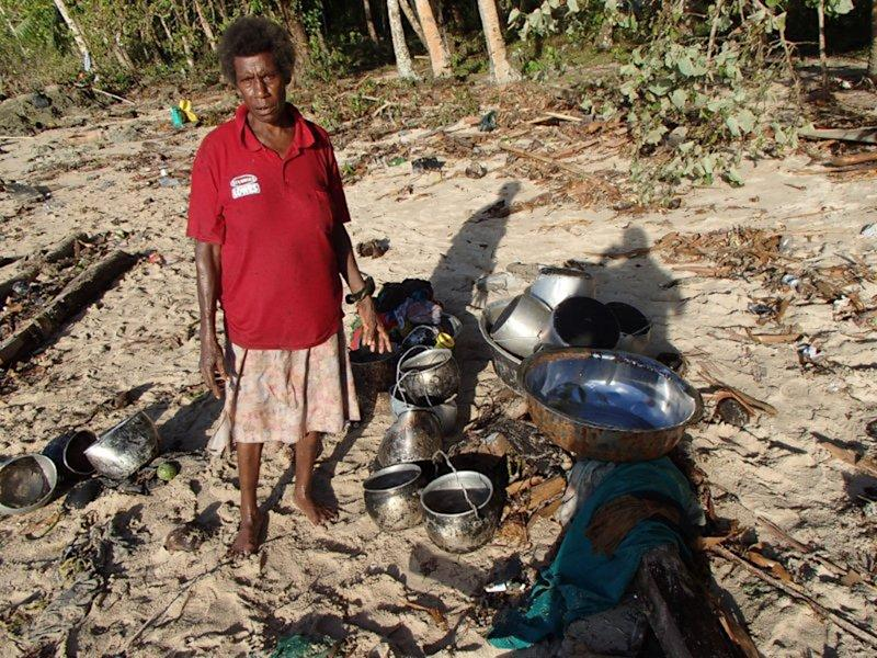 In this Wednesday Feb. 6, 2013 photo provided by World Vision, a woman stands next to her belongings she found along a beach at Venga village after tsunami hit Temotu province, Solomon Islands. The damage seen is part of a survey by the assessment crew of the aid organization World Vision. A strong aftershock rattled the Solomon Islands on Friday, Feb. 8, 2013, hampering relief efforts to tsunami-ravaged villages and forcing the South Pacific nation's Prime Minister Gordon Darcy Lilo to forgo a visit to the stricken area where nine deaths have been confirmed. (AP Photo/World Vision)
