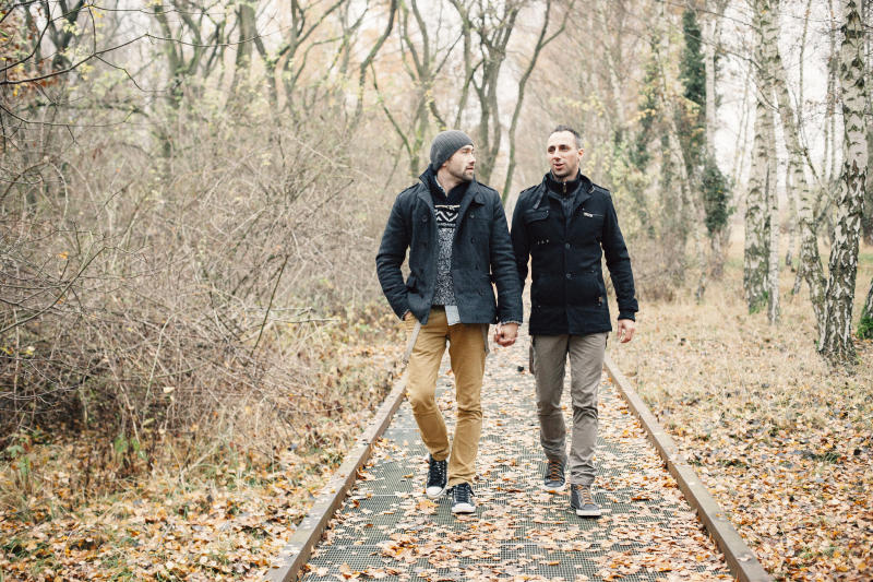 gay couple take a walk through autumn forest