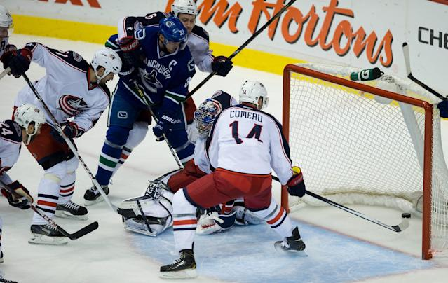 Vancouver Canucks' Henrik Sedin, third left, of Sweden, scores a goal past Columbus Blue Jackets' goalie Sergei Bobrovsky, of Russia, as Derek MacKenzie, from left, Fedor Tyutin, of Russia, Nikita Nikitin, of Russia, and Blake Comeau, right, watch during second period NHL hockey action in Vancouver, British Columbia, Friday, Nov. 22, 2013. (AP Photo/The Canadian Press, Darryl Dyck)