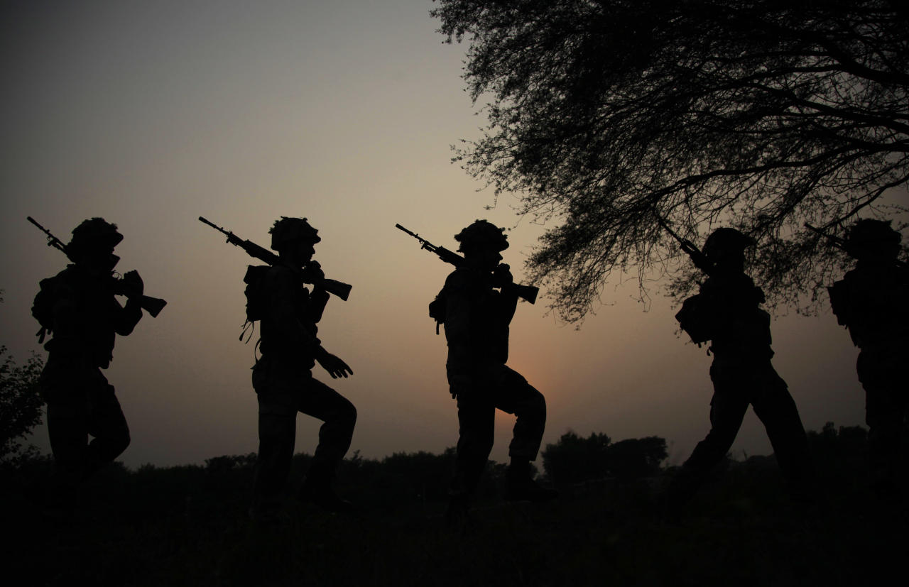 FILE - In this Oct. 2, 2016 file photo, Indian army soldiers patrol near the Line of Control in Nowshera sector, about 90 kilometers from Jammu, India. As India considers its response to the suicide car bombing of a paramilitary convoy in Kashmir that killed dozens of soldiers on Feb. 14, 2019, a retired military commander who oversaw a much-lauded military strike against neighboring Pakistan in 2016 has urged caution. (AP Photo/Channi Anand, File)
