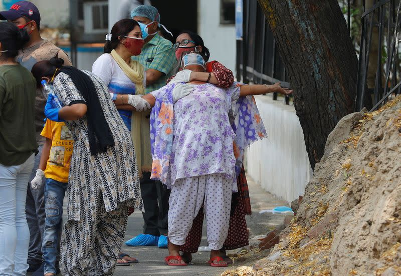 A woman mourns after seeing the body of her son who died due to the coronavirus disease, outside a mortuary of a COVID-19 hospital in New Delhi