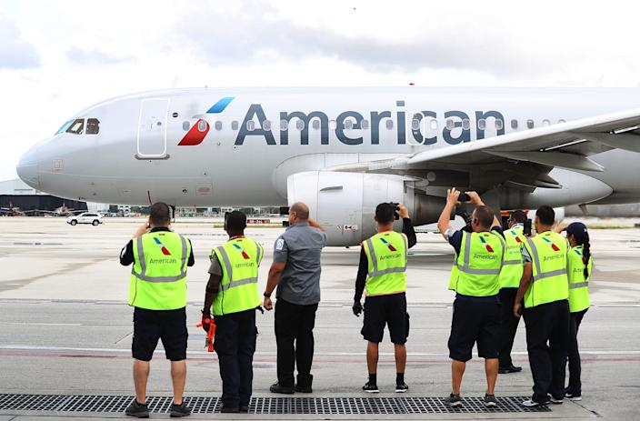 Employees watch as American Airlines Flight 903 prepares for take off from Miami in 2016.