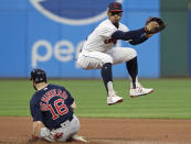 Cleveland Indians' Francisco Lindor, right, looks to first base after getting out Boston Red Sox's Andrew Benintendi, left, at second base in the fourth inning of a baseball game, Monday, Aug. 12, 2019, in Cleveland. Christian Vazquez was out at first base for a double play. (AP Photo/Tony Dejak)