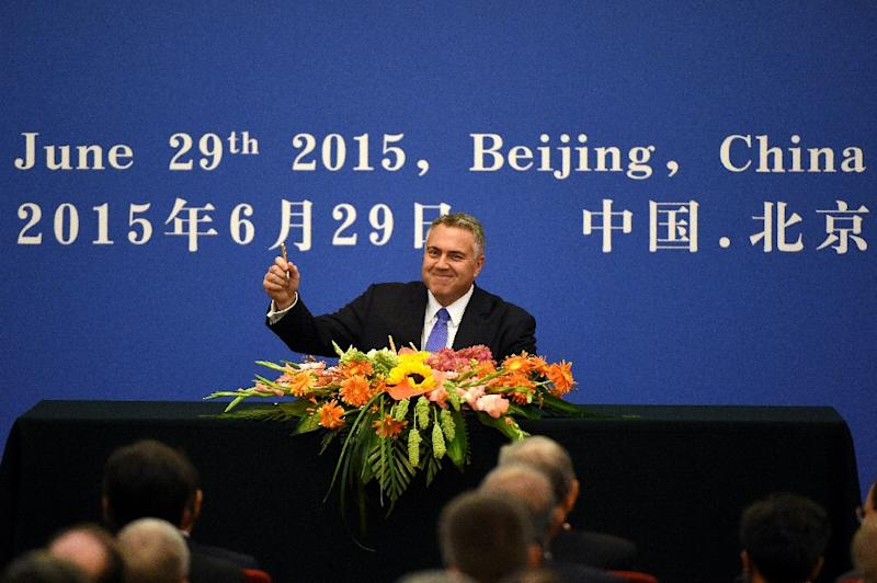 Australia's Treasurer Joe Hockey (C) holds up his pen as he becomes the first to sign an articles of association to help set up the Asian Infrastructure Investment Bank during a ceremony at the Great Hall of the People in Beijing on June 29, 2015 (AFP Photo/Wang Zhao)