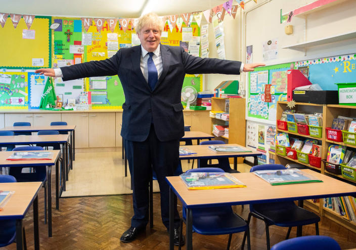 Image: Britain's Prime Minister Boris Johnson poses with his arms out-stretched in a classroom as he visits St Joseph's Catholic Primary School in Upminster, east London (Lucy Young / AFP - Getty Images)