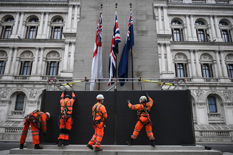 "LONDON, ENGLAND - JUNE 11: Workers erect a protective barrier around the Cenotaph in anticipation of protests tomorrow on June 11, 2020 in London, England. Outside the Houses of Parliament, the statue of former Prime Minister Winston Churchill was spray-painted with the words ""was a racist"" amid anti-racism protests over the weekend. In Bristol, protesters toppled a statue of Edward Colston, a 17th-century slave-trader, and tossed it into the harbor. (Photo by Peter Summers/Getty Images)"
