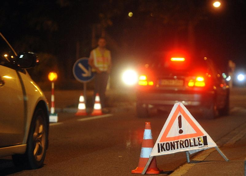 Border police stand near a sign reading 'control' as cars wait at the German-Austrian border near Lindau on September 13, 2015 (AFP Photo/Stefan Puchner)