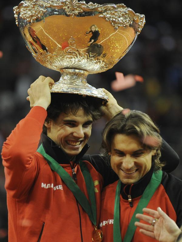 Spain's Rafael Nadal (L) celebrates holding the David Cup trophy next to teammate David Ferrer after winning the Davis Cup final against Argentina at La Cartuja Olympic stadium in Sevilla on December 4, 2011. Spain's Rafael Nadal got the winning point as Spain won a fifth Davis Cup. The world number two beat Argentina's Juan Martin del Potro to give the hosts an unbeatable 3-1 lead, rallying from a set down to see off the 2009 US Open champion 1-6, 6-4, 6-1, 7-6 (7/0). (Photo by Javier Soriano Afp Photo / Cristina Quicler/AFP/Getty Images)