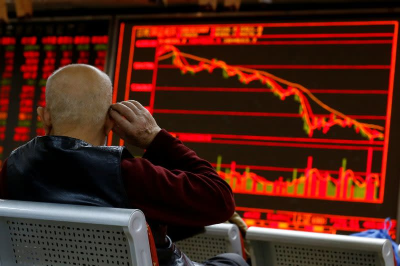 FILE PHOTO: An investor sits in front of a board showing stock information at a brokerage office in Beijing
