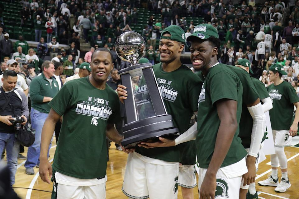 Michigan State's Cassius Winston, left, Xavier Tillman Sr., center, and Gabe Brown with the Big Ten trophy after  their 80-69 win against Ohio State on Sunday, March 8, 2020 at the Breslin Center.