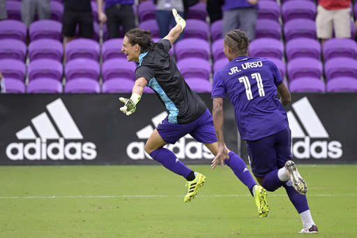 Orlando City defender Rodrigo Schlegel, left, celebrates after blocking the final New York City FC penalty kick during overtime of an MLS soccer playoff match, Saturday, Nov. 21, 2020, in Orlando, Fla. Schlegal was sent in to substitute for goalkeeper Pedro Gallese who was ejected after getting his second yellow card. (AP Photo/Phelan M. Ebenhack)