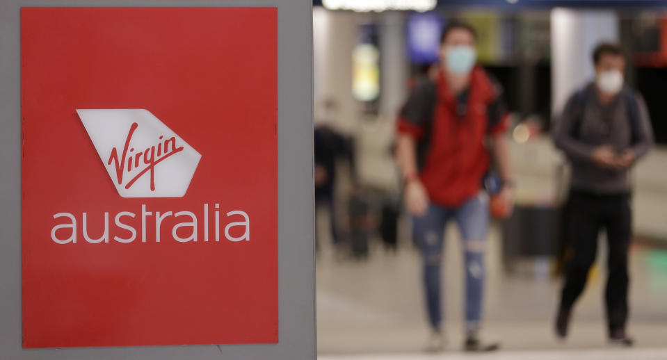 FILE - In this Aug. 5, 2020, file photo, passengers walk past a Virgin Australia sign at Sydney Airport in Sydney. Virgin Australia's creditors agreed Friday to sell the airline to Boston-based Bain Capital in a deal that will see the carrier cut 3,000 jobs and end many of its international flights. (AP Photo/Rick Rycroft, File)