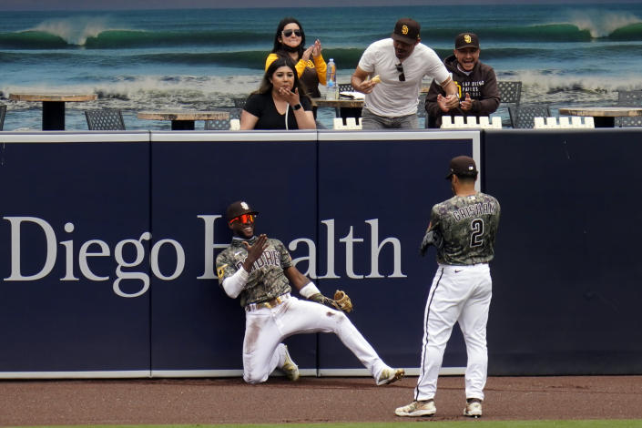 San Diego Padres left fielder Jurickson Profar, below right, reacts with teammate center fielder Trent Grisham after making a catch at the wall for the out on San Francisco Giants' Mike Tauchman during the first inning of a baseball game Sunday, May 2, 2021, in San Diego. (AP Photo/Gregory Bull)
