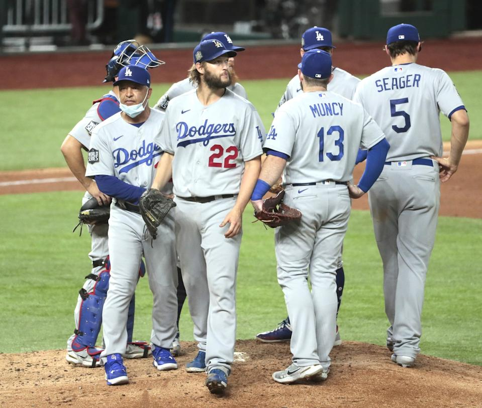 Clayton Kershaw walks off the mound surrounded by teammates