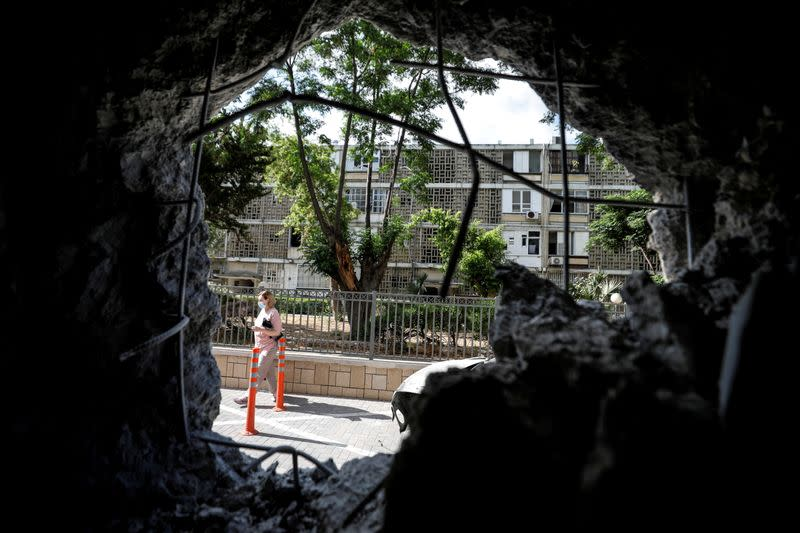 FILE PHOTO: A woman is seen through a wall of a residential building which was damaged by a rocket launched overnight from the Gaza Strip, in Ashkelon