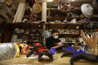 Venetian artisan mask maker Gualtiero Dall'Osto works in his workshop in Venice, Italy, Saturday, Jan. 30, 2021. In another year, masks would be an accepted sign of gaiety in Venice, an accessory worn for games, parties and crowds. Since the onset of the COVID-19 pandemic face masks are worn now to protect, not amuse. (AP Photo/Antonio Calanni)