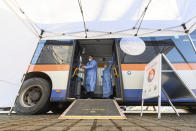Medical staff prepare a bus, containing a so-called rolling vaccination centre for a the test run in Grosshartmannsdorf, Germany, Sunday, Feb. 21, 2021. Mobile vaccination centers will be used to vaccinate people against the coronavirus and the COVID-19 disease in three municipalities of German federal state Saxony. (Robert Michael/dpa via AP)