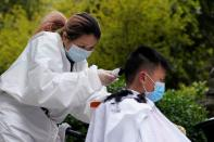 Barber Xiong Juan cuts a customer's hair at a residential compound in Wuhan